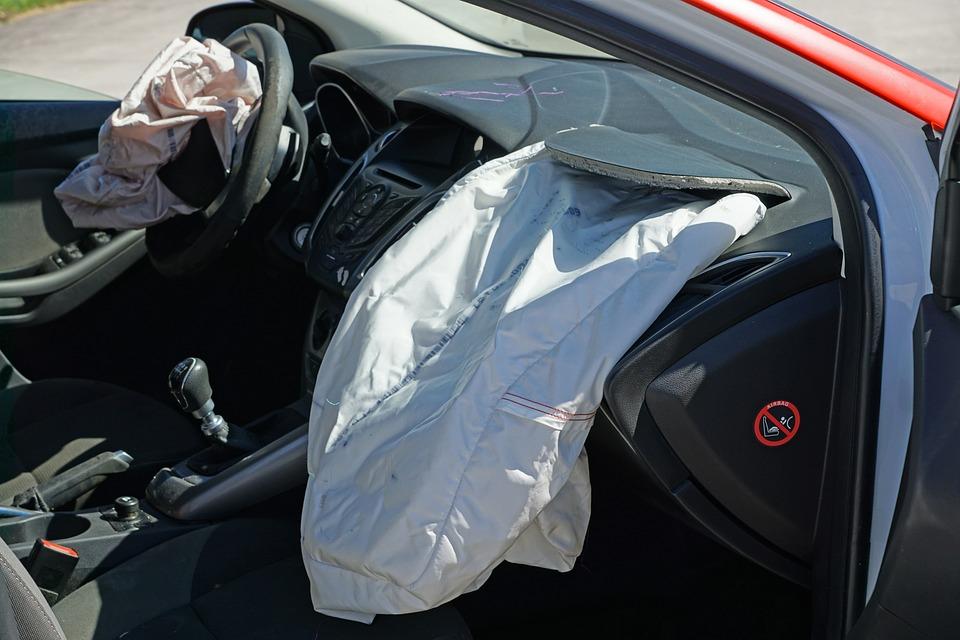 deska rozdzielcza samochodu osobowego z wystrzelonymi poduszkami zarówno u kierowcy jak i pasażera