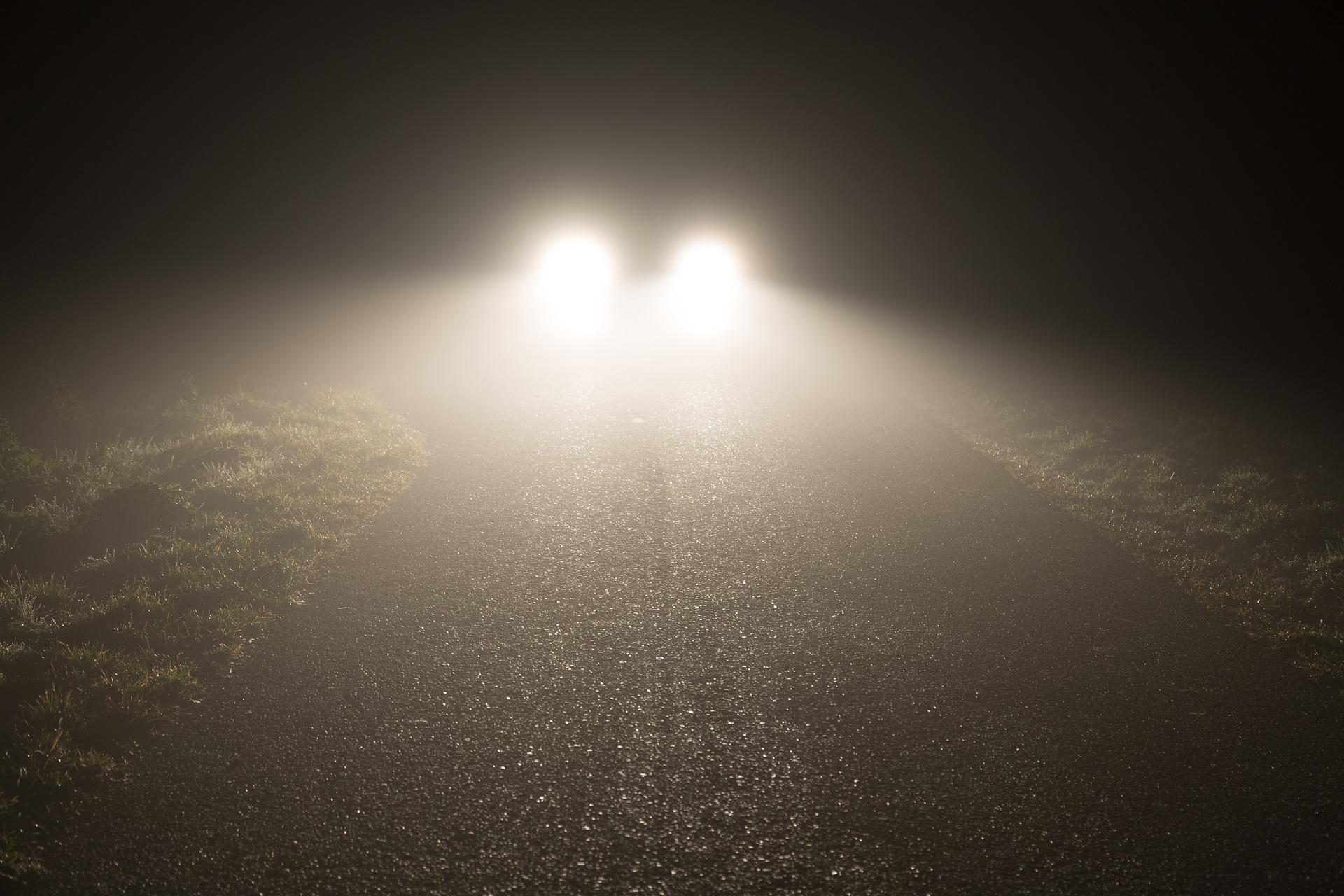 samochód oświetlający drogę w nocy
